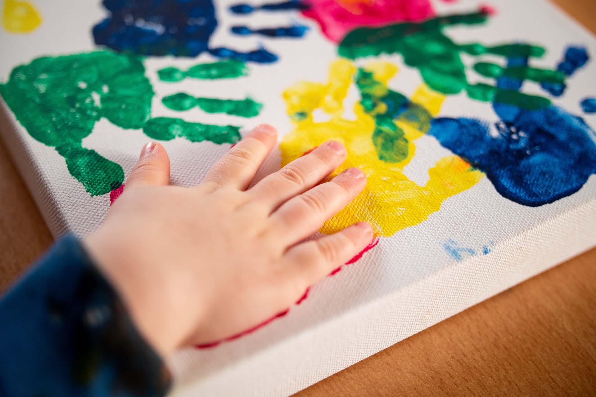 Ergotherapie Wachter Banner Pädiatrie Kinderhand mit Farbe
